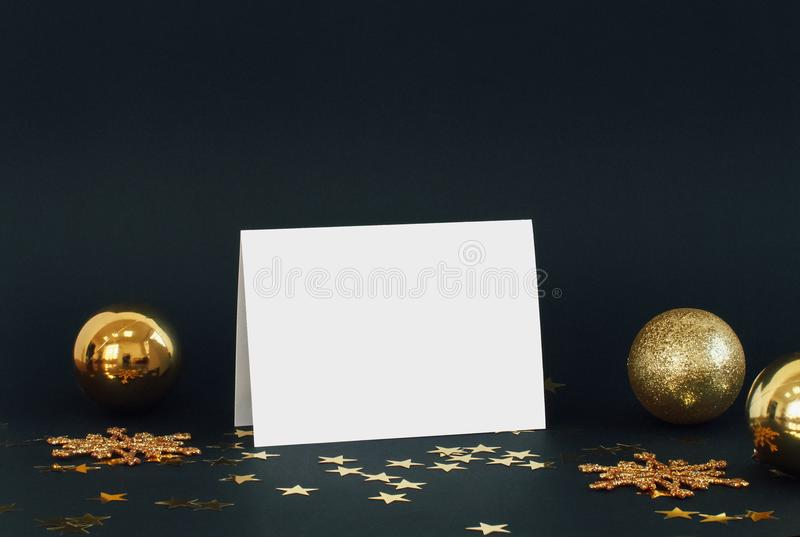 Zombaria acima do cartão no fundo escuro com confetes dos flocos de neve, das quinquilharias, do sino e das estrelas do brilho da fotografia de stock royalty free