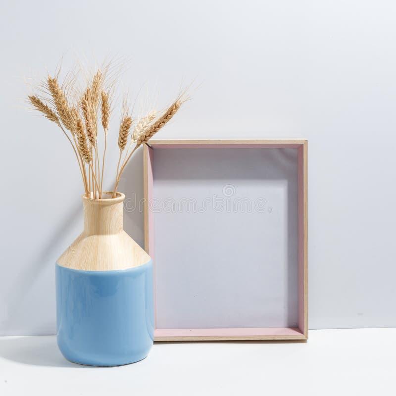 Zombaria acima do quadro e dos spikelets brancos do trigo no vaso azul na biblioteca ou na mesa Conceito de Minimalistic imagens de stock royalty free