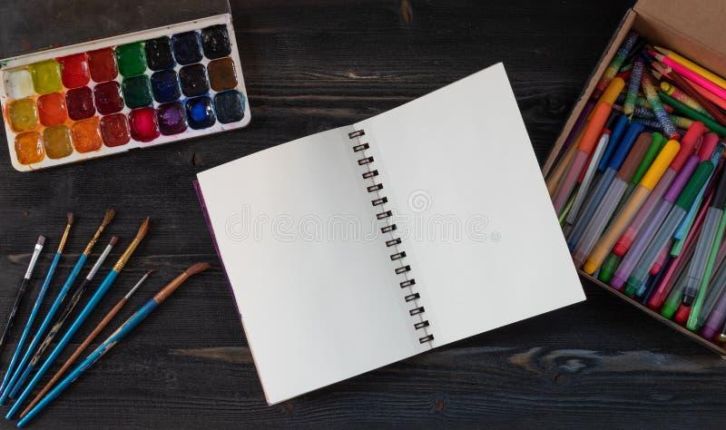 Zombaria acima Espa?o criativo Espa?o de trabalho do artista na tabela de madeira do vintage: a aquarela, Livro Branco, escovas d imagens de stock