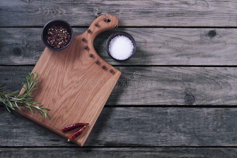 Zombaria acima para o menu ou a receita do restaurante Placa de corte de madeira com sal e pimenta no fundo rústico cinzento cópi imagens de stock royalty free