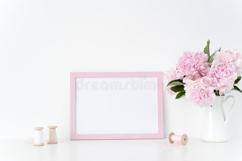 A zombaria cor-de-rosa do quadro da paisagem acima com peônias cor-de-rosa e as fitas de seda ao lado do quadro, overlay seu cita fotos de stock royalty free