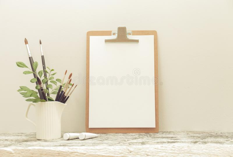 A zombaria da placa de grampeamento acima na tabela e nas escovas brancas da arte com efeito do embaçamento imagens de stock
