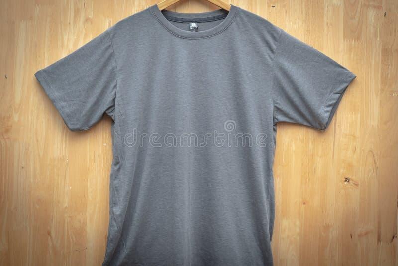 Zombaria lisa do pescoço do círculo do t-shirt curto cinzento da luva acima da opinião de parte dianteira traseira de madeira da  foto de stock