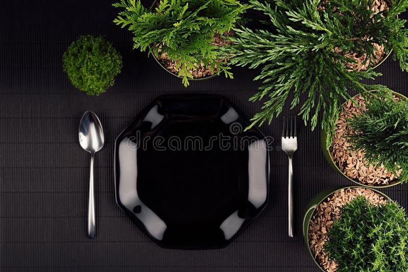 Zombaria minimalistic moderna escura do menu do restaurante de Eco acima com a placa lustrosa preta, colher, forquilha, plantas v imagem de stock
