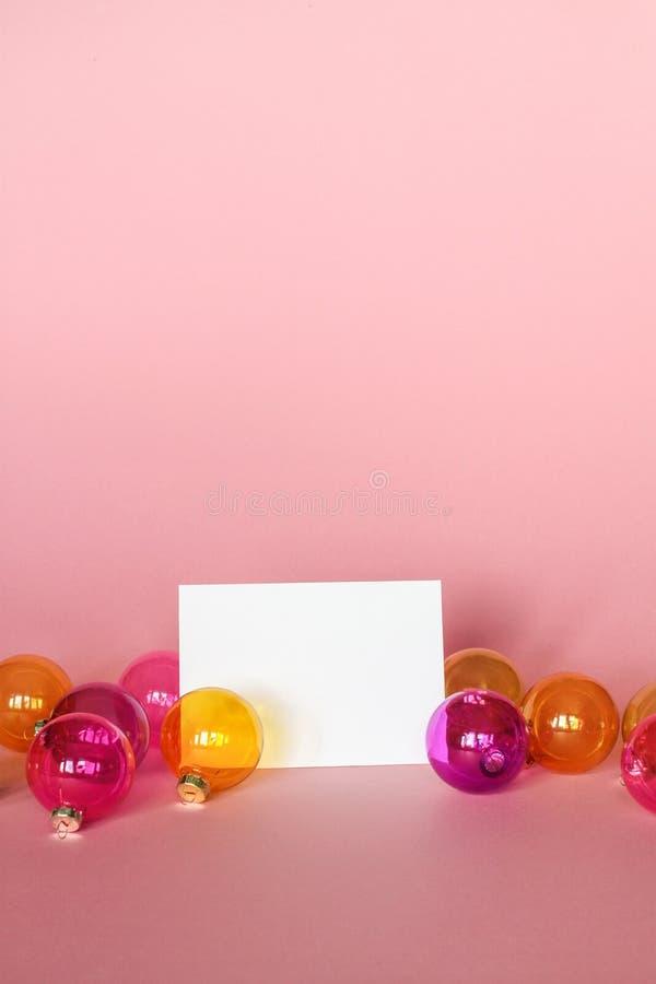 Zombe acima com o cartão do convite na luz - fundo cor-de-rosa com ornamento do Natal Cartão e colorfull Chri de vidro translúcid imagens de stock royalty free