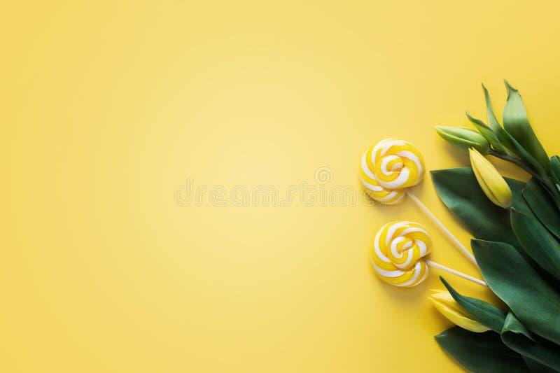 Zombe acima das tulipas amarelas e dos doces de dois pirulitos fotografia de stock