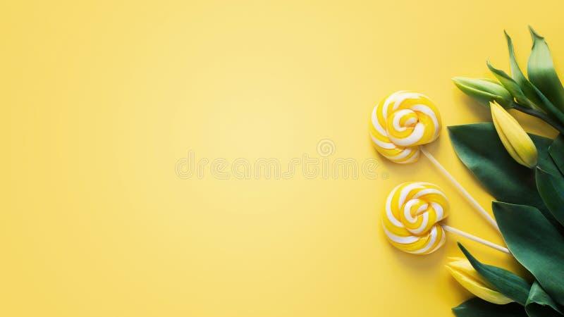 Zombe acima das tulipas e do pirulito amarelos sobre o amarelo fotografia de stock