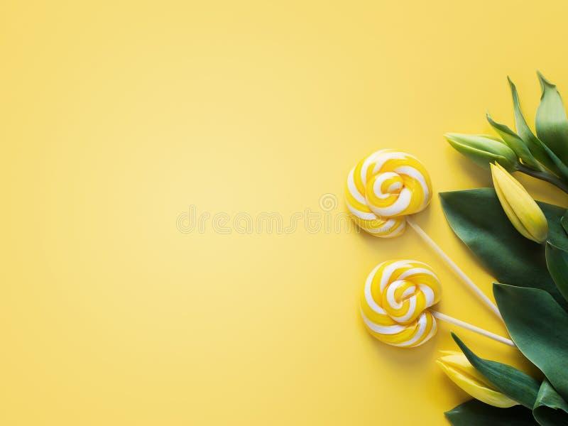 Zombe acima das tulipas e do pirulito amarelos sobre o amarelo foto de stock