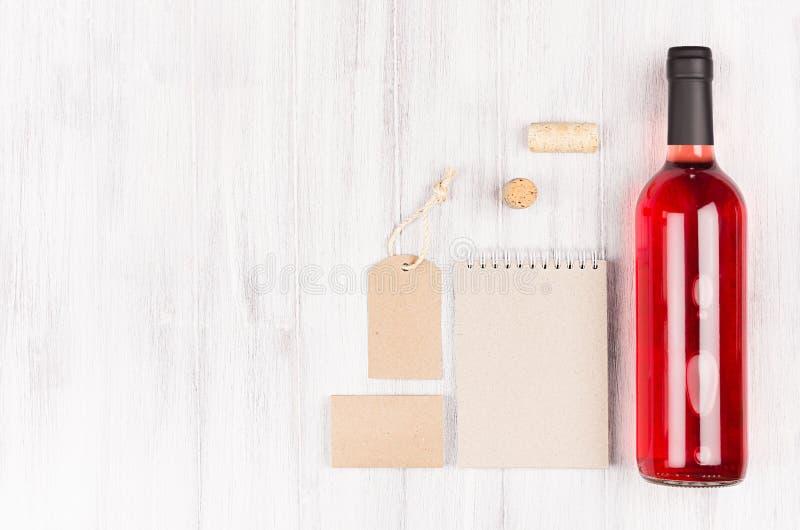 Zombe acima de kraft bege vazio que empacota, artigos de papelaria, mercadoria com vinho cor-de-rosa da garrafa no fundo de madei fotografia de stock