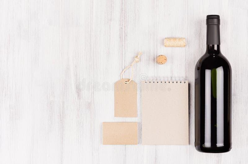 Zombe acima de kraft bege vazio que empacota, artigos de papelaria, mercadoria com vinho tinto da garrafa no fundo de madeira bra imagens de stock