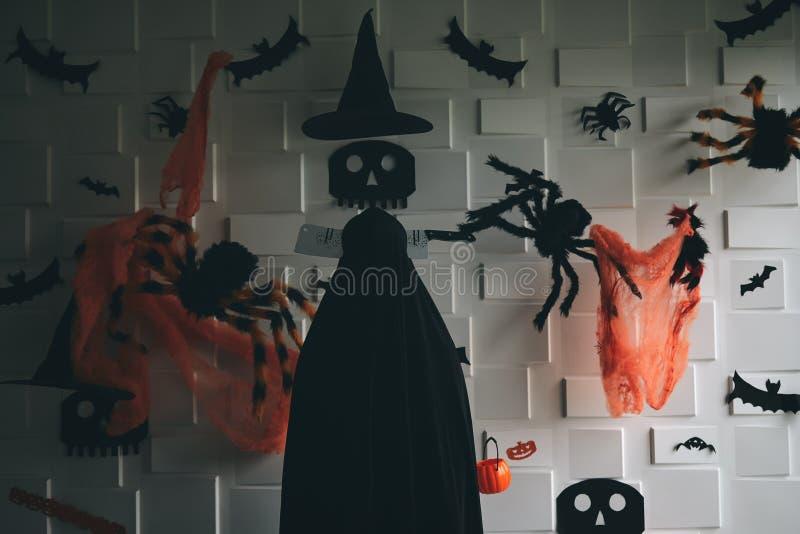 Zombi mort avec le couperet sur la tête se tenant dans la salle sombre de ton avec les articles décorés tels que le crâne, l'arai photo stock