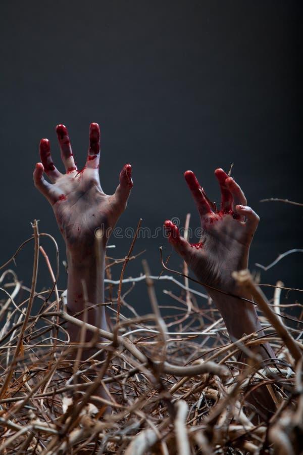 Zombie που τεντώνει τα ανατριχιαστικά χέρια του από τον τάφο στοκ φωτογραφίες
