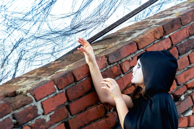 A zombie behind barbed wire pulls his hands to the sky to freedom. Prison and freedom. Catch the monster. A girl dressed as a stock images