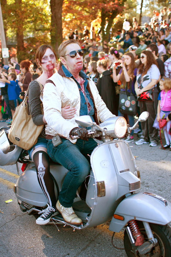 Zombie Couple Rides Scooter In Halloween Parade royalty free stock photos