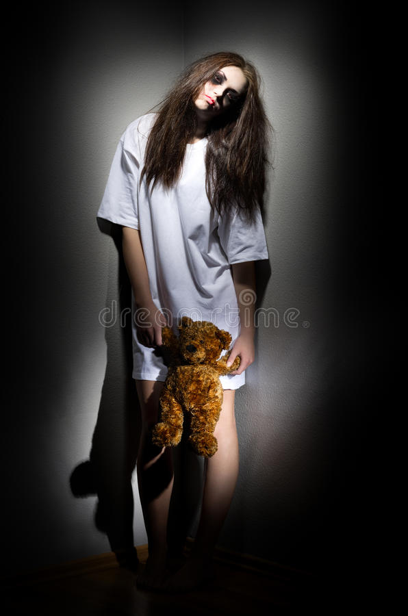 Zombie girl with teddy bear stock images