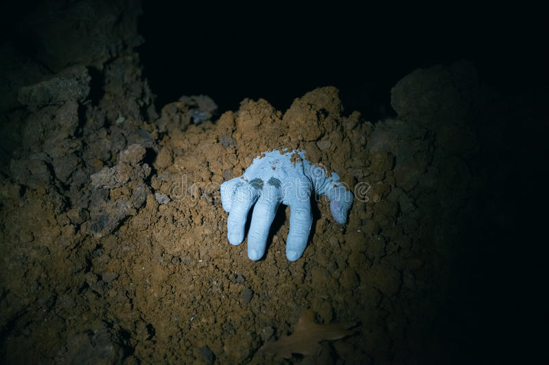 Zombie hand coming out of his grave stock images