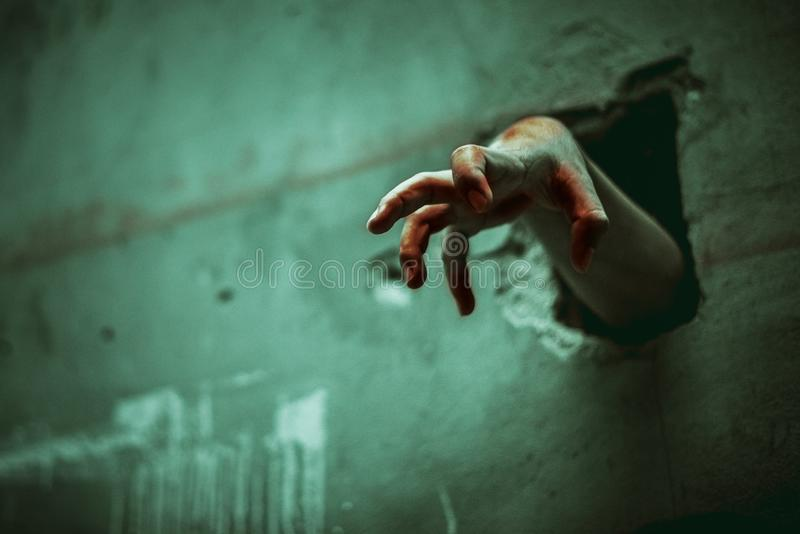 Zombie hand through the cracked wall. Horror and scary film concept. Halloween day theme. Green tone like ghost movie stock images