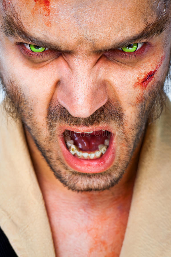 Zombie scary eyes. Portrait of sinister man wolf with scary green artificial eyes, mouth open stock photos