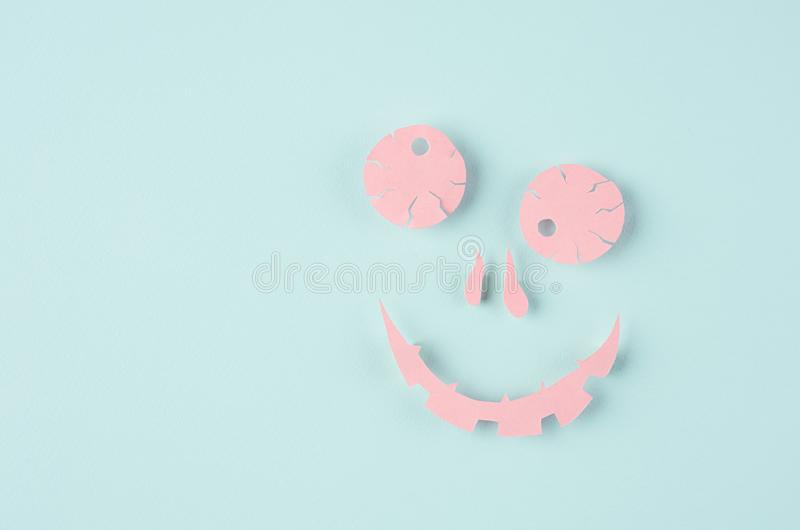 Zombie smile pink face, silhouette of origami cut paper on mint color, as modern simple minimalist halloween background. stock photography