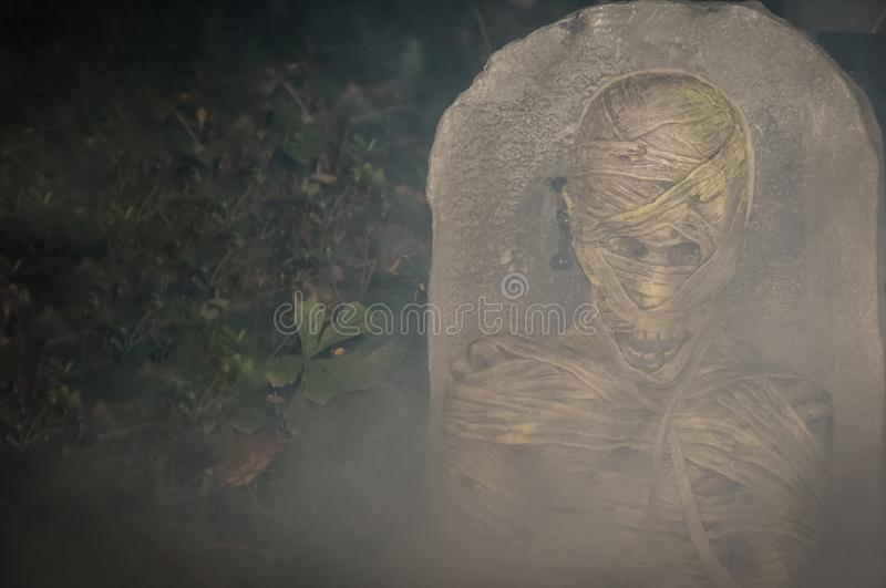 Zombie by a Tombstone. A zombie by a headstone surrounded by smoke stock image