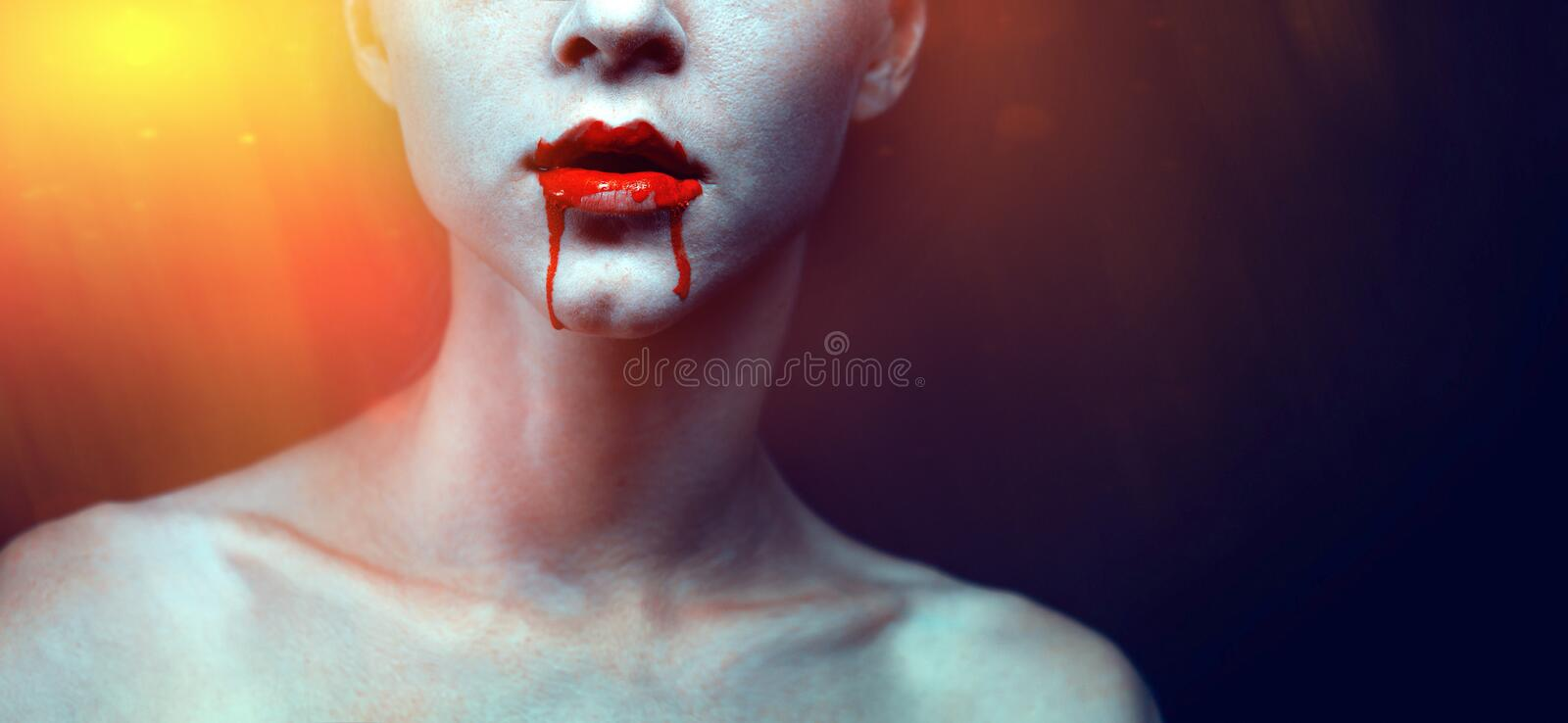 Zombie vampire woman with bloody lips and blue skin portrait. Fashion glamour halloween art design concept stock photography