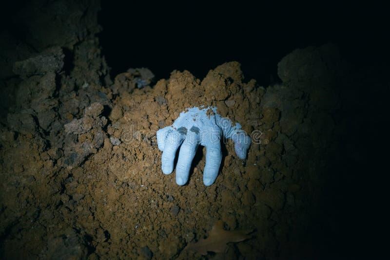Zombiehand die uit zijn graf komen stock afbeeldingen