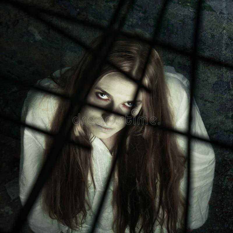 Zombiemädchen hinter Gitter stockbild