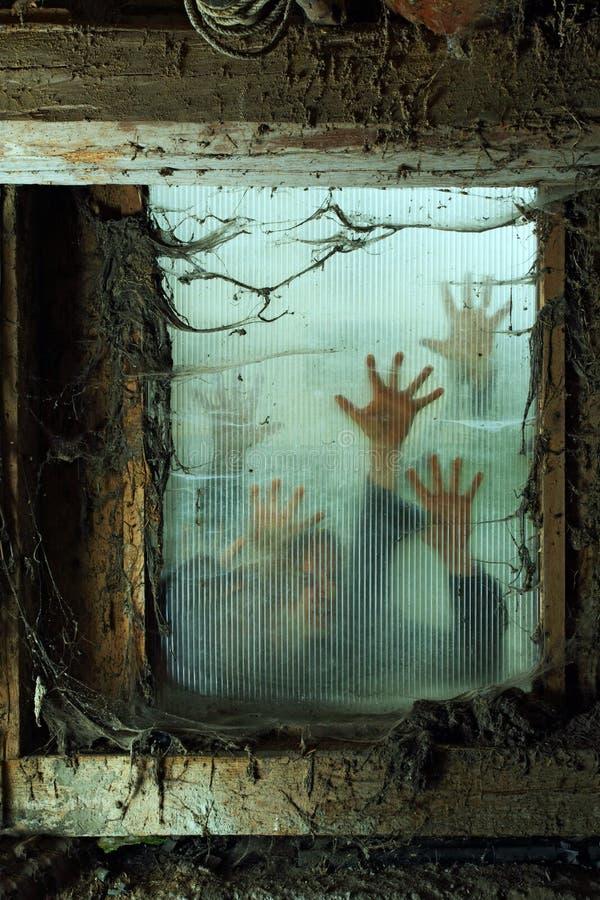 Zombies utanför ett fönster royaltyfri bild