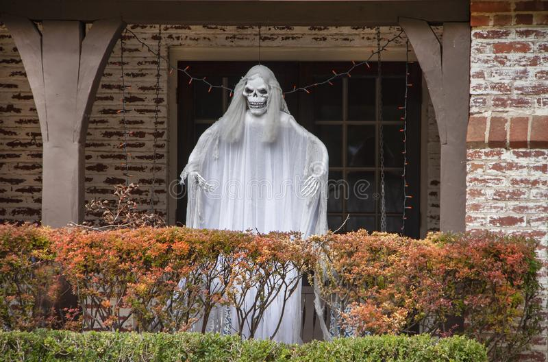 Zombiespook die zich op portiek achter de herfst gekleurde haag voor Halloween-decoratie bevinden royalty-vrije stock foto's