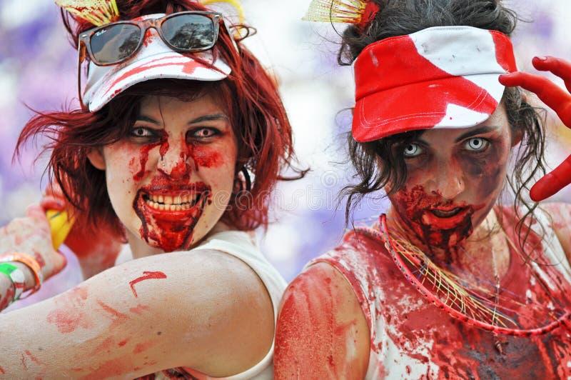 Zombis del monstruo de las muchachas de los deportes del bádminton que asustan a la muchedumbre en el paseo del zombi fotos de archivo libres de regalías