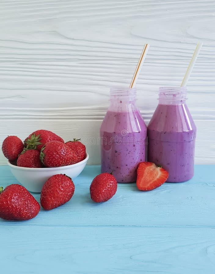 Zomer van de het ontbijthanddoek van de aardbei smoothies de verse sappige smaak op een roze houten achtergrond stock afbeeldingen