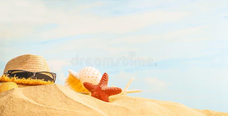 Zomer, zeeschelp, zeester, zonnebril en strohoed op zandig strand met zonnige kleurrijke blauwe hemelachtergrond en exemplaarruim royalty-vrije stock fotografie