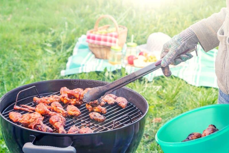 Zomerpicknick in de binnenplaats - Kokende kippenvleugels op een ronde grill dicht omhoog stock afbeeldingen