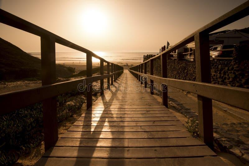 Zomerpijler tijdens een kleurrijke mooie zonsondergang wordt gevangen die loop en ga naar oceaan en zandig strand de vakantie en  stock fotografie