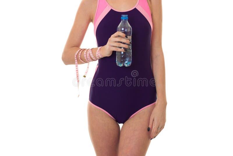 Zomerportret van jonge seksuele dame in volledig die lengtezwempak met flessenwater en maatregelenband op whit wordt geïsoleerd stock afbeeldingen