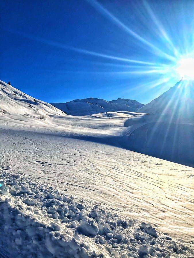 Zon achter de gesneeuwde bergen royalty-vrije stock foto's