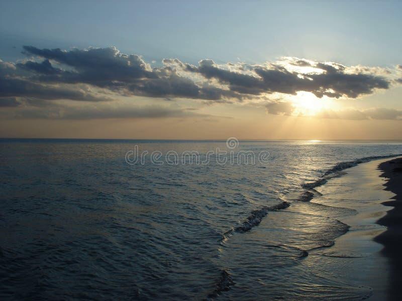Zon in de wolken bij zonsondergang door het overzees royalty-vrije stock fotografie