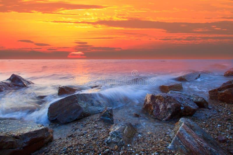 Zon die bij rots overzees strand wordt geplaatst stock afbeeldingen