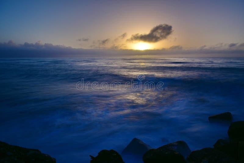 Zon die boven de horizon plaatsen zoals die van Zuidelijk Golfbreker het Bekijken Platform in Greymouth, Nieuw Zeeland wordt beke stock afbeeldingen