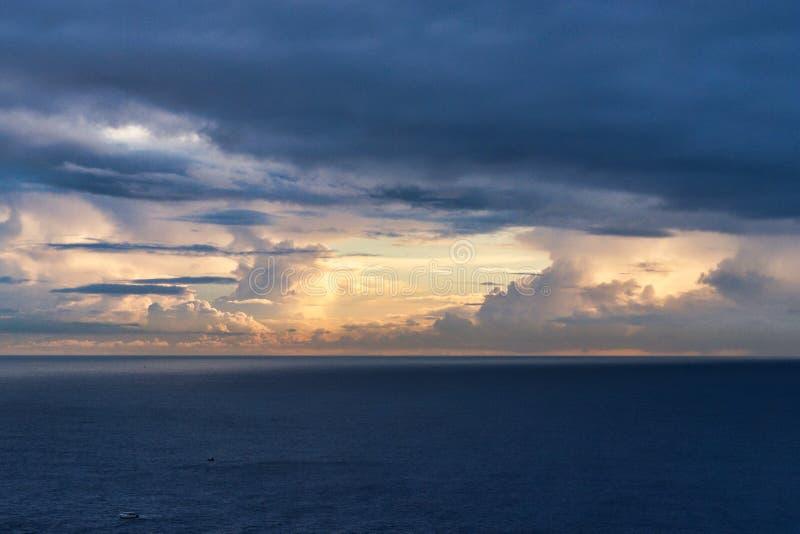 Zon die door Donkere Wolken over Vreedzame Oceaan glanst stock fotografie