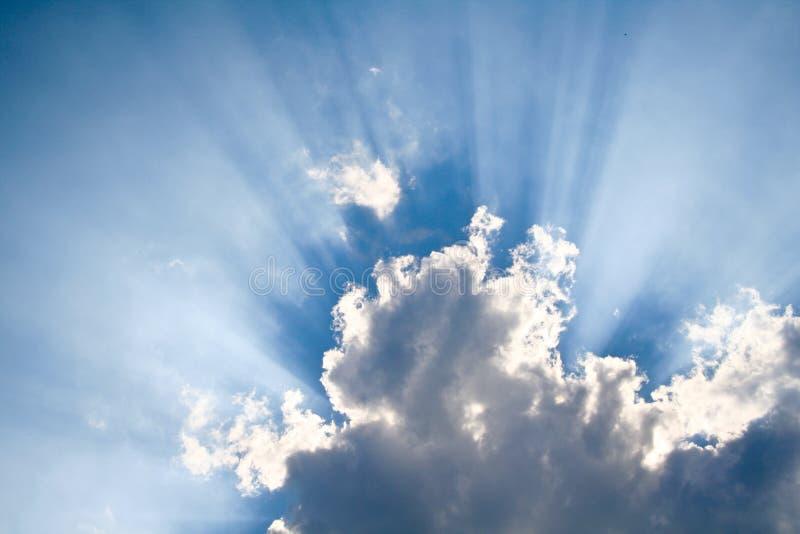 Zon die door wolken glanst stock foto