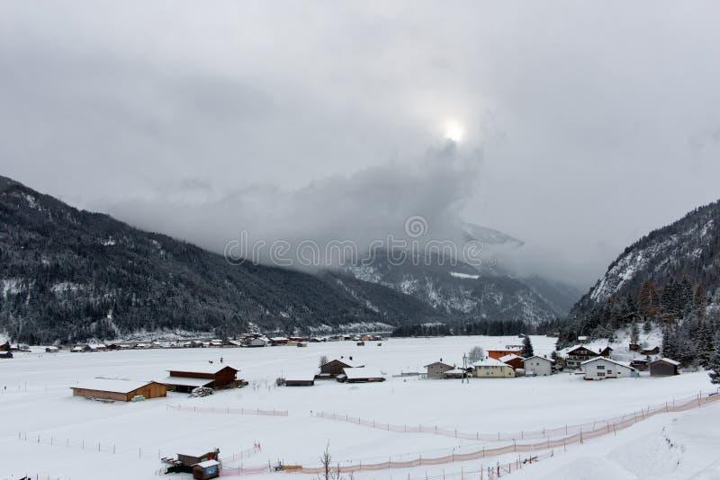 Zon die op Achenkirch, Oostenrijk proberen te glanzen stock afbeelding