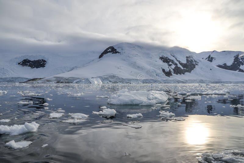Zon die over de bergen in Antarctica plaatsen stock foto's