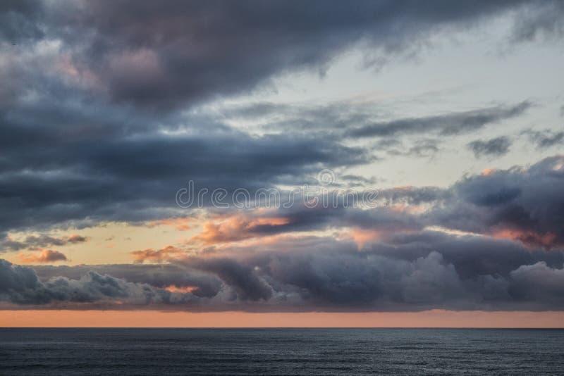 Zon die over de oceaan wordt geplaatst stock afbeeldingen