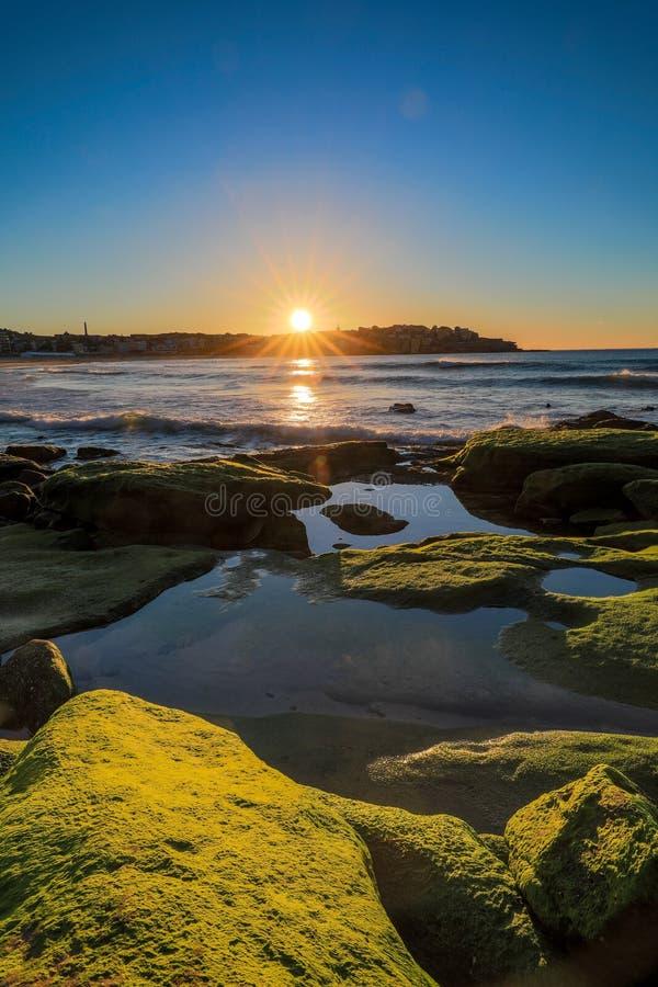 Zon die over oceaan en rotsachtige kustlijn tegen blauwe hemel toenemen royalty-vrije stock foto's