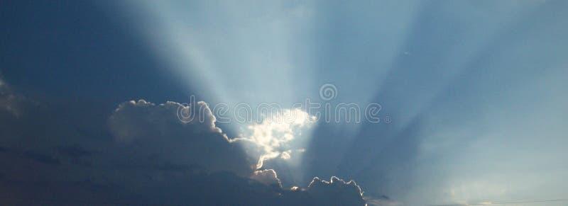 Zon die van Achter Wolken uitstralen stock afbeelding