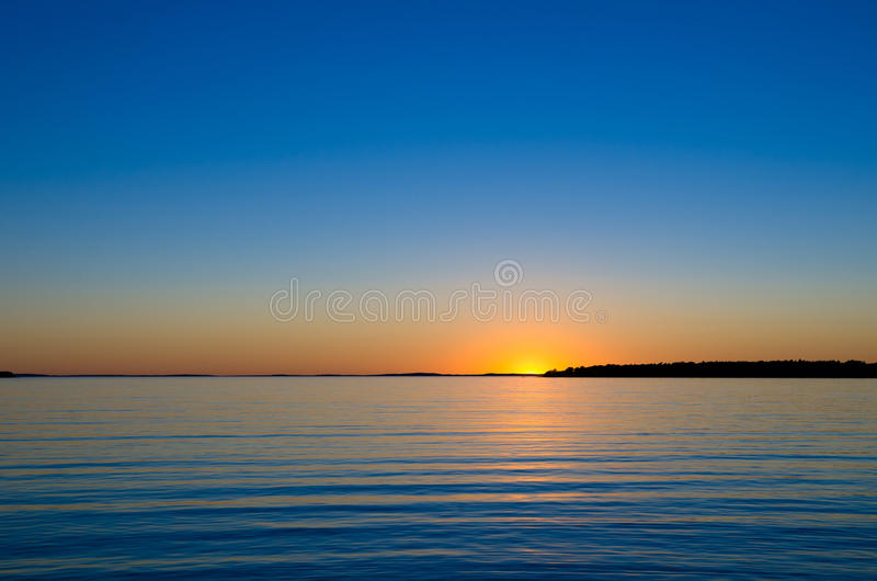 Zon door de horizon stock afbeeldingen