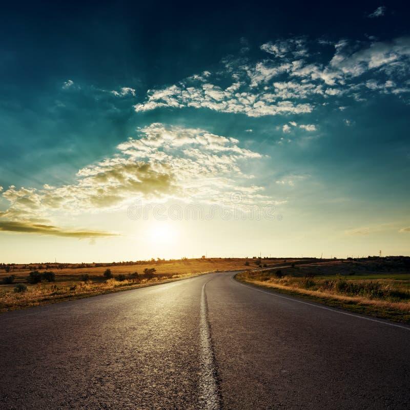 Zon in dramatische wolken over asfaltweg, zonsondergangtijd royalty-vrije stock foto