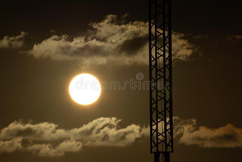 Zon en silhouet van een communicatie antenne stock foto