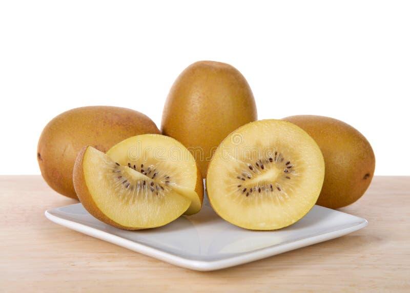 Zon Gouden die kiwi op een plaat met geheel erachter fruit op lijst wordt gesneden royalty-vrije stock afbeelding
